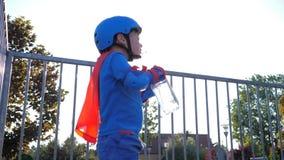 Bambini acqua potabile, ragazzo nel costume del supereroe con la bevanda di raffreddamento in recipiente di plastica su aria aper