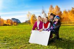 Bambini adolescenti che mostrano il bordo in bianco del cartello Fotografia Stock