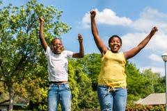Bambini africani che saltano insieme nel cortile Immagini Stock