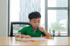 Bambini al pensiero della tavola di studio Scherzi la tenuta una penna e dei wi di un taccuino fotografia stock