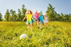 Bambini allegri che corrono alla palla nel campo Immagini Stock Libere da Diritti