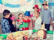 Bambini allegri che danno i presente alla ragazza durante il partito Fotografia Stock