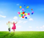 Bambini allegri che giocano i palloni all'aperto Immagini Stock Libere da Diritti