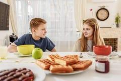 Bambini allegri che mangiano alimento in cucina Fotografia Stock Libera da Diritti