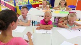 Bambini allegri che si siedono alla classe di scuola stock footage