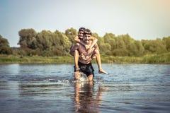 Bambini allegri divertendosi sul fiume durante le vacanze estive in campagna che simbolizza infanzia spensierata fotografie stock