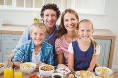 Bambini allegri e genitori che mangiano prima colazione dalla tavola immagine stock