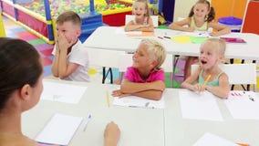Bambini attenti che si siedono ed insegnante d'ascolto nella classe della scuola elementare archivi video