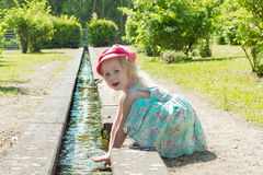 Bambini Bambina che gioca con acqua in un'insenatura un giorno soleggiato caldo Fotografia Stock