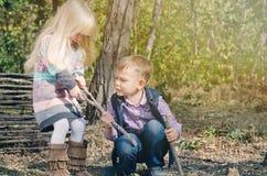 Bambini bianchi che combattono per il bastone secco Immagine Stock