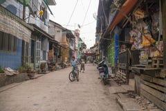 Bambini birmani con le biciclette che giocano sulla via, Mawlamyine, Birmania, marzo 2012: Un gioco birmano di due bambini su una immagini stock libere da diritti