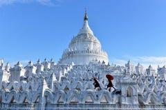Bambini buddisti con correre rosso degli ombrelli e degli abiti fotografie stock