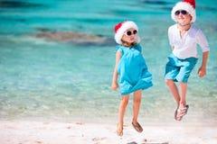 Bambini in cappelli della Santa alla spiaggia Fotografia Stock Libera da Diritti