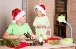 Bambini in cappelli di Santa che fanno le decorazioni di Natale Faccia Cristo fotografia stock