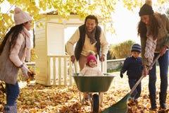Bambini che aiutano i genitori a raccogliere Autumn Leaves In Garden Fotografia Stock