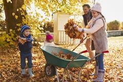 Bambini che aiutano padre To Collect Autumn Leaves In Garden Immagini Stock Libere da Diritti
