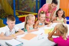 Bambini che attingono lezione nella classe della scuola elementare Fotografia Stock