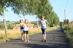 Bambini che camminano sulla strada con gli alberi Immagini Stock Libere da Diritti