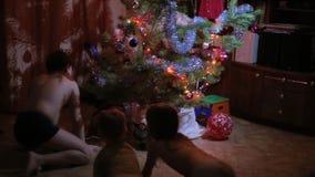 Bambini che cercano i regali sotto l'albero di Natale video d archivio