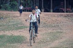 Bambini che ciclano vicino al tempio di Bakong fotografia stock