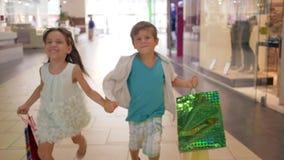 Bambini che comperano, ragazzino allegro con la ragazza con i lotti dei pacchetti che corre che si tengono per mano dopo gli acqu video d archivio