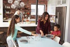 Bambini che contribuiscono a porre da portare in tavola per il pasto della famiglia immagini stock libere da diritti