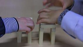 Bambini che costruiscono torre dai blocchetti del giocattolo stock footage
