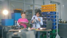 Bambini che costruiscono un robot su una tavola Concetto di istruzione tecnica stock footage