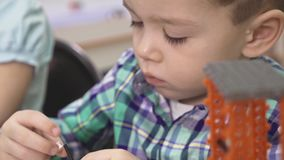Bambini che creano i robot alla scuola, istruzione del gambo Sviluppo iniziale, diy, innovazione, concetto moderno di tecnologia archivi video