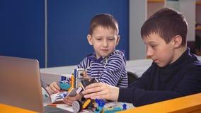 Bambini che creano i robot alla scuola, istruzione del gambo Sviluppo iniziale, diy, innovazione, concetto moderno di tecnologia stock footage