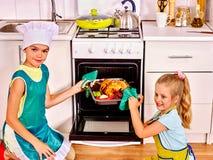 Bambini che cucinano pollo alla cucina Fotografia Stock