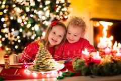 Bambini che cuociono sulla notte di Natale Immagini Stock
