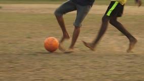 Bambini che danno dei calci ad un pallone da calcio bianco in India archivi video