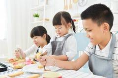 Bambini che decorano i biscotti immagine stock libera da diritti