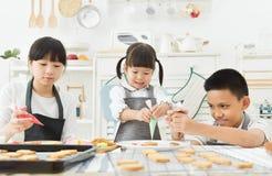 Bambini che decorano i biscotti immagini stock