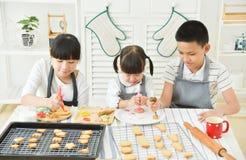 Bambini che decorano i biscotti fotografie stock