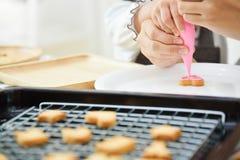 Bambini che decorano sul biscotto di forma del cuore Fotografia Stock