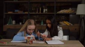 Bambini che dipingono con i pennelli e gli acquerelli stock footage