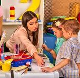 Bambini che dipingono e che riuniscono Lezione del mestiere a scuola primaria Immagine Stock