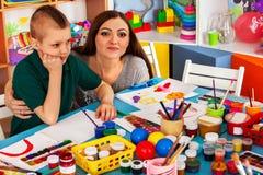 Bambini che dipingono e che riuniscono Lezione del mestiere a scuola primaria Fotografie Stock