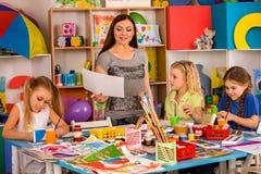 Bambini che dipingono e che riuniscono Lezione del mestiere a scuola primaria Immagini Stock