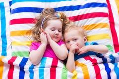 Bambini che dormono sotto la coperta variopinta Immagine Stock