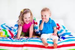 Bambini che dormono sotto la coperta variopinta Fotografie Stock