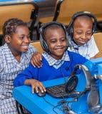 Bambini che esaminano computer nella stanza di classe della scuola in Africa fotografie stock libere da diritti