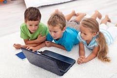 Bambini che esaminano computer portatile Fotografie Stock Libere da Diritti