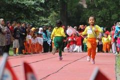 Bambini che eseguono la concorrenza del relè fotografia stock