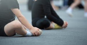 Bambini che fanno allungando gli esercizi sul pavimento immagine stock