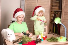 Bambini che fanno le decorazioni di Natale con l'uccello ed il gatto sulla t fotografia stock