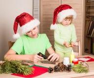 Bambini che fanno le decorazioni di Natale Faccia la decorazione di natale fotografie stock libere da diritti