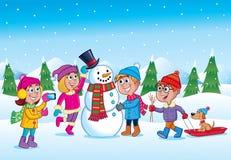 Bambini che fanno un pupazzo di neve durante l'orario invernale fotografia stock libera da diritti